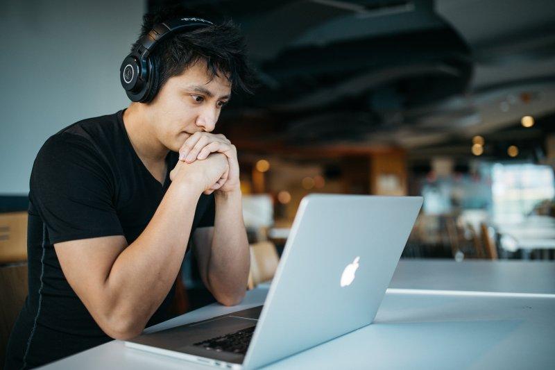 Un trabajador remoto está en una cafetería con su ordenador portátil y unos auriculares puestos