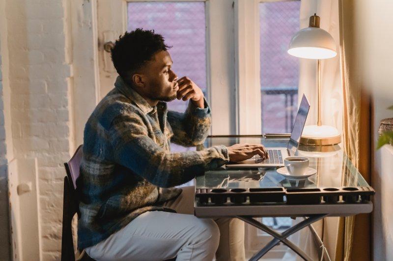 Un hombre está en su casa y con el ordenador busca ofertas de trabajo