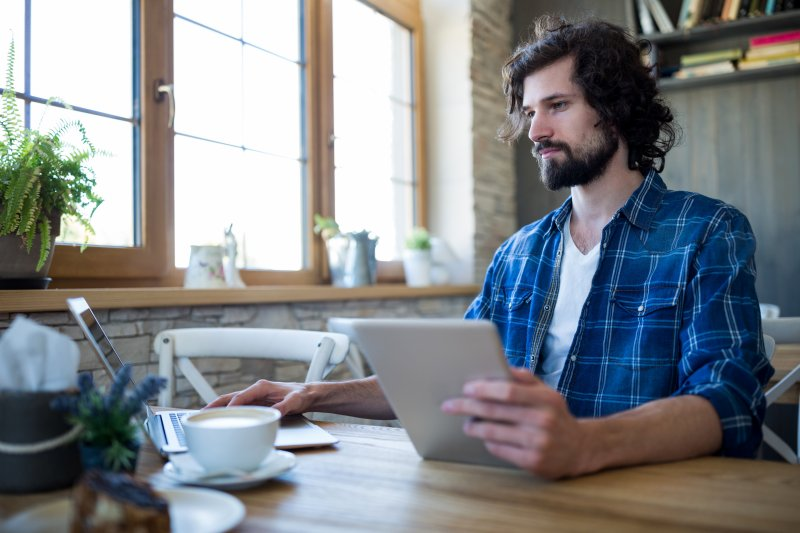 Un hombre trabaja en remoto en una cafetería con un ordenador portátil i una tablet