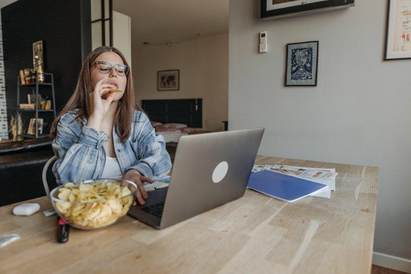Una mujer come patatas fritas en su casa mientras trabaja con el ordenador portátil