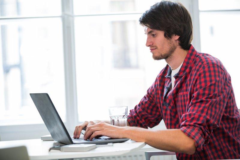 Un hombre joven escribe en su laptop para enviar el archivo de su currículum por email
