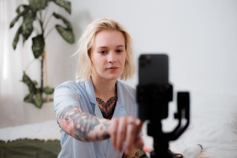 Una mujer joven pulsa en la pantalla del teléfono móvil para empezar a grabar su currículum en video para TikTok