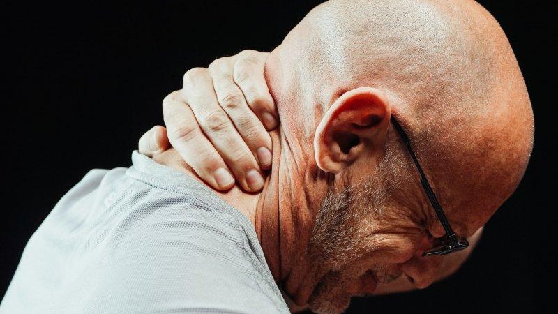 Un hombre se toca el cuello con señales evidentes de dolor