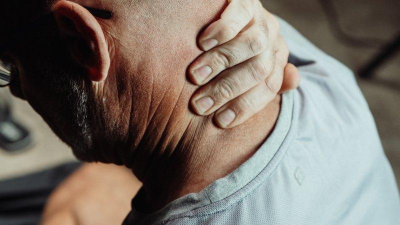 Un hombre sufre dolor de cuello a causa de la posición que tiene delante el ordenador