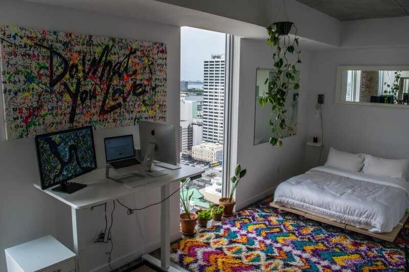 Dormitorio con un escritorio elevado, dos ordenadores y otra pantalla