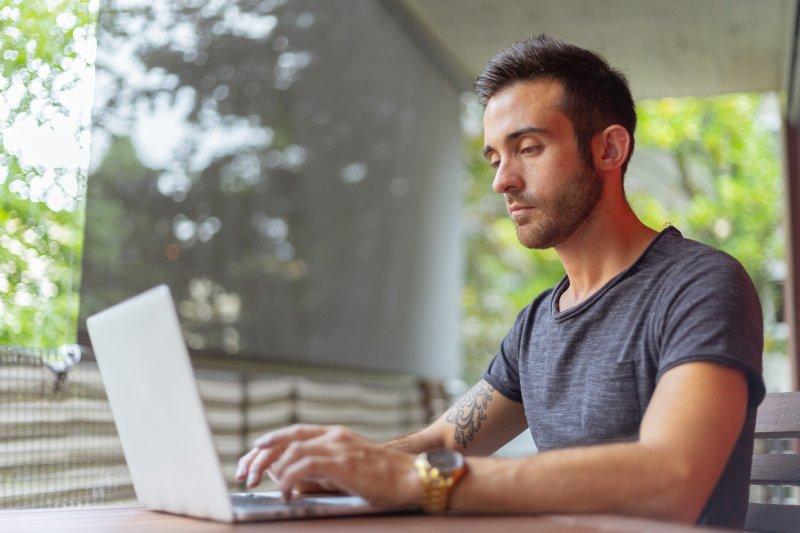 Un chico escribe en el ordenador portátil mientras trabaja desde casa