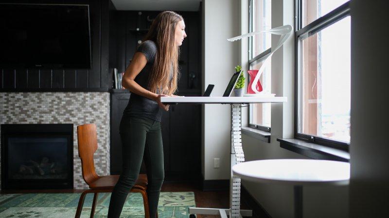 Una mujer trabaja en su casa con un ordenador portátil enun escritorio de altura regulable