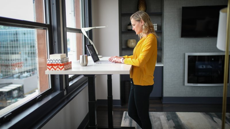 Una mujer está en su casa escribiendo en el laptop en una mesa de pie