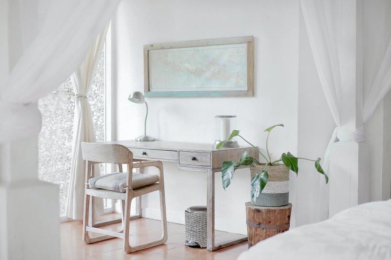 Mesa y silla de escritorio que forman una home office en un dormitorio