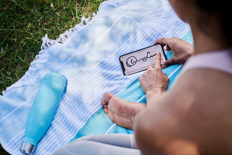 Una mujer utiliza una aplicación de firma de documentos en su teléfono móvil
