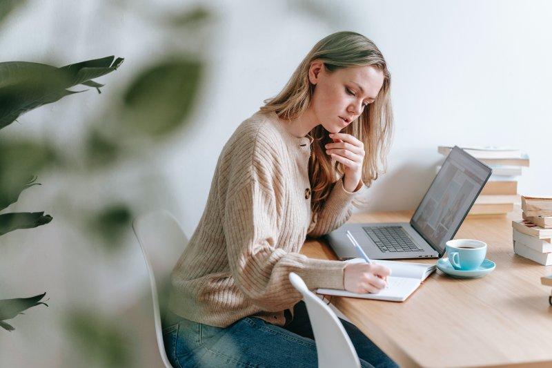 Chica que teletrabaja escribe en una libreta y tiene el ordenador portátil delante
