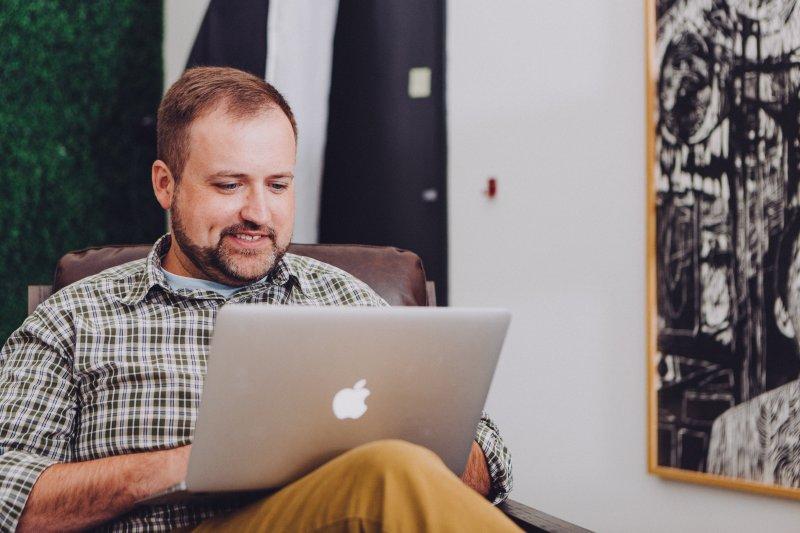 Un hombre sentado en una butaca de su casa escribe en su ordenador Apple
