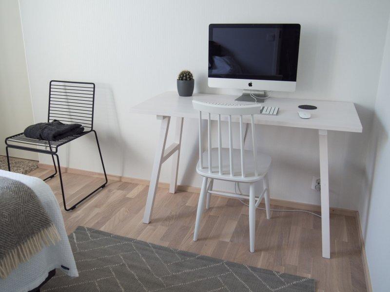 Home office en un dormitorio con un escritorio, una silla y un ordenador Apple