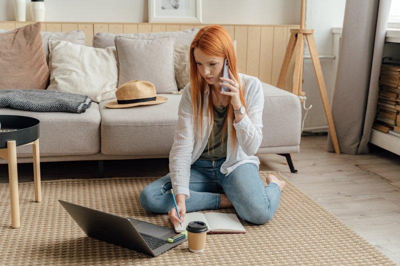 Una mujer trabaja con su ordenador portátil en su casa sobre una alfombra mientras habla por teléfono y escribe en una libreta
