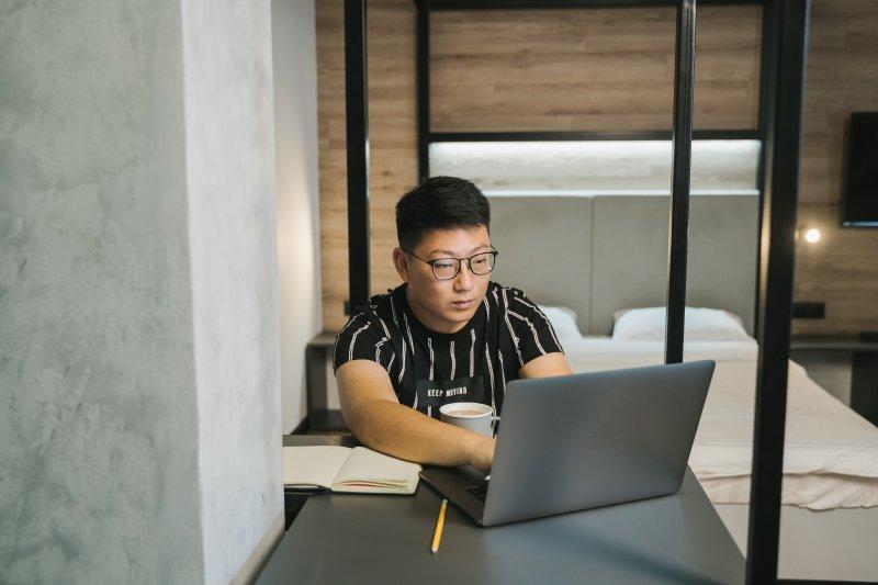 Un hombre asiático trabaja con su laptop desde su casa