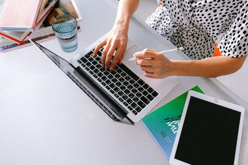 Mujer utilizando un ordenador portátil y una tablet para trabajar en casa
