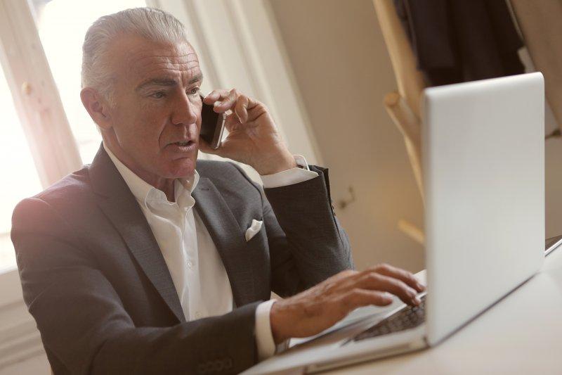 Llamada de un jefe de la empresa a un trabajador mientras consulta el ordenador portátil