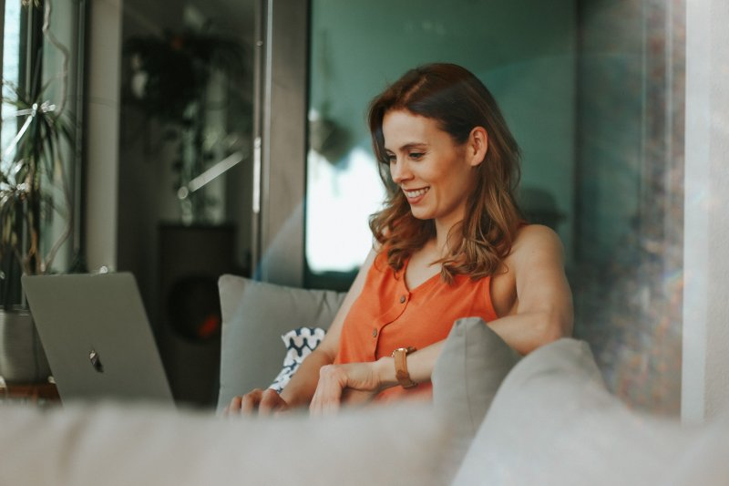 Una mujer motivada con su trabajo escribe en el ordenador portátil en su casa.