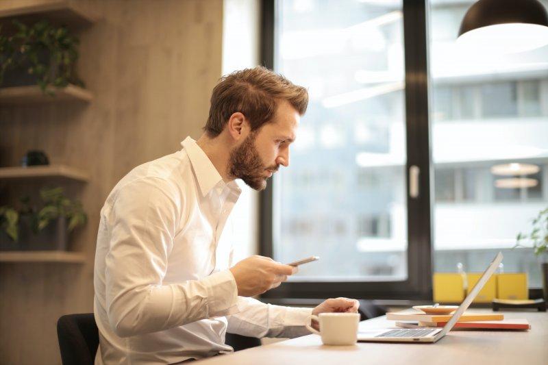 Un hombre mira su ordenador portátil mientras está pendiente en su mano del teléfono móvil