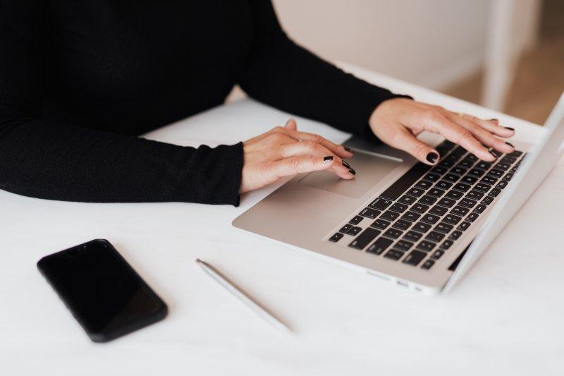 Una mujer escribe en un ordenador portátil con el teléfono móvil al lado