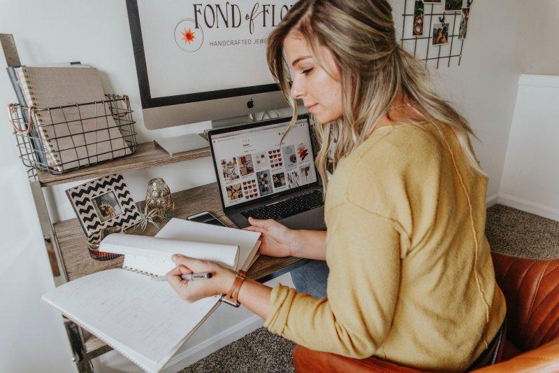 Una mujer hace trabajo online en su casa con un ordenador portátil