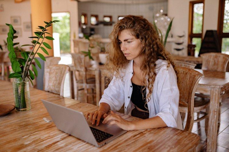 Una mujer realiza trabajo remoto en su casa con un ordenador portátil