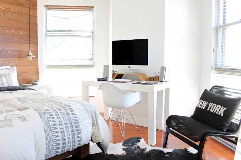 Oficina configurada en un dormitorio, con un escritorio, silla y ordenador.