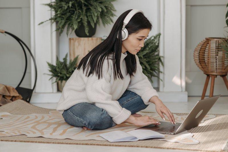 Una mujer escucha música con unos auriculares mientras trabaja con su ordenador portátil sobre una alfombra
