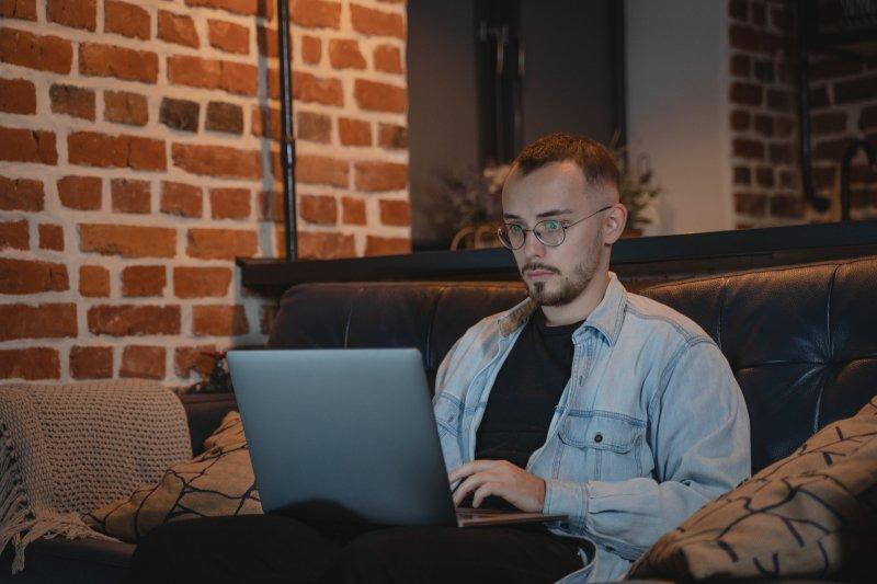 Un chico escribe en el ordenador portátil en el sofá de su casa