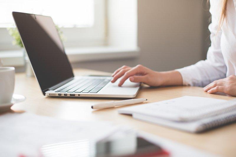 Una mujer teclea el ordenador portátil que utiliza para trabajar en casa
