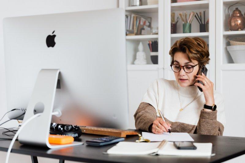 Una mujer en su casa escribe mientras habla por teléfono con el ordenador delante