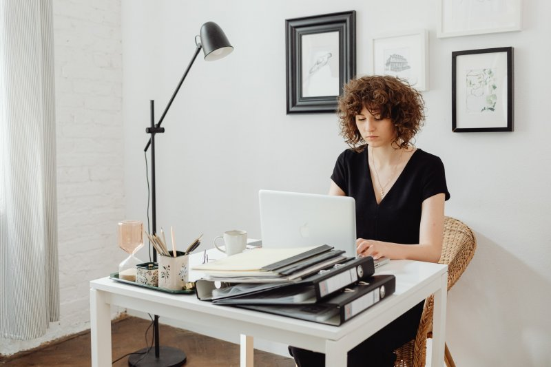 Mujer joven escribe en un ordenador portátil en su domicilio