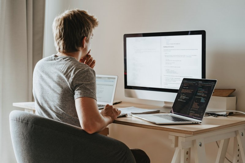 Programador trabajando desde su casa observa una de las pantallas de ordenador que tiene