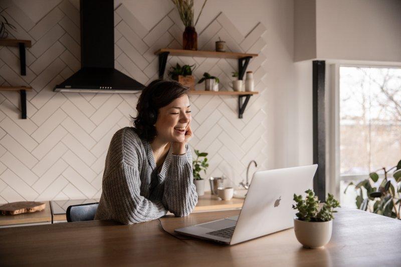Una mujer sonrie mientras realiza una videollamada de trabajo con su ordenador portátil.
