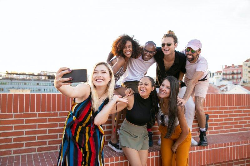 Un grupo de amigos de chicos y chicas se hacen un selfie en una terraza