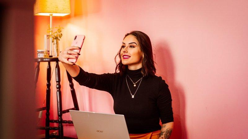 Una mujer joven sonríe para hacerse un selfie con su teléfono móvil