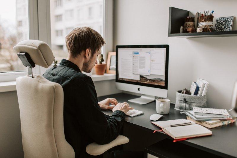 chico trabajando en su casa con el ordenador y sentado en una silla ergonomica