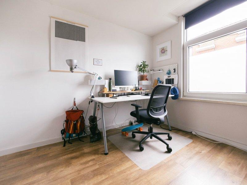 Despacho en casa de un teletrabajador con una silla con ruedas y una mesa