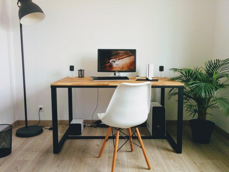 Espacio de trabajo en una habitación de la casa con una silla sin ruedas, un escritorio y un ordenador
