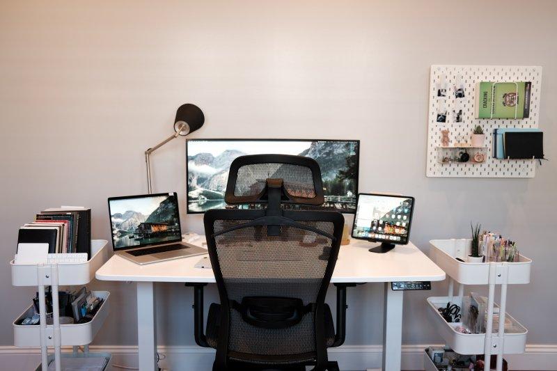 Un espacio de trabajo en casa con una silla ergonómica de respaldo alto y tres monitores