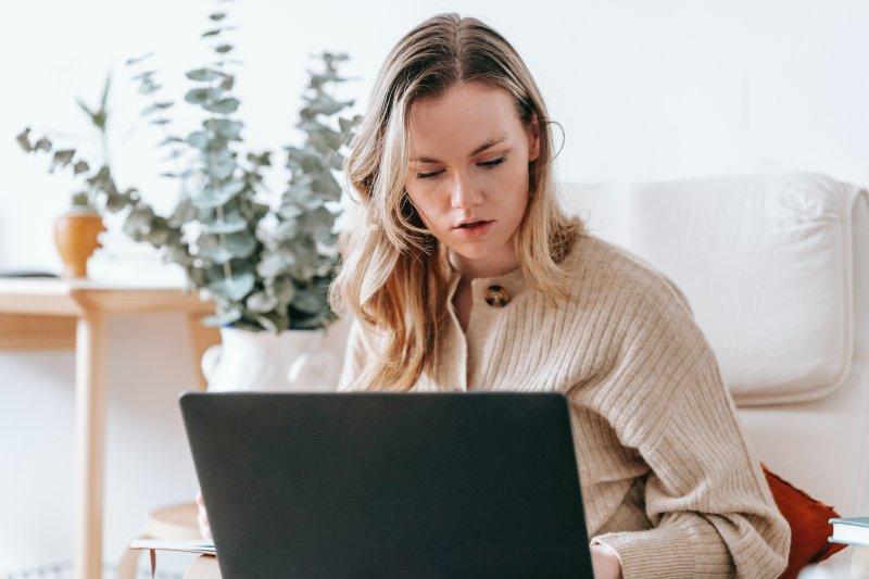 una mujer teletrabaja con un ordenador portátil sentada en un sillon.