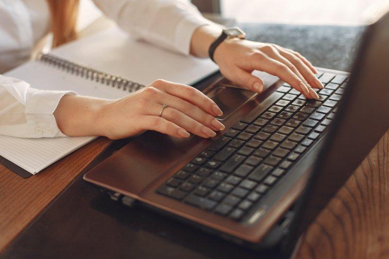 Unas manos de mujer teclean un ordenador portátil.