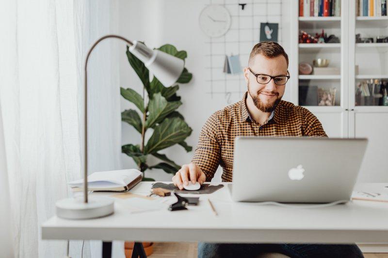 Un hombre trabaja en su casa con el ordenador portátil