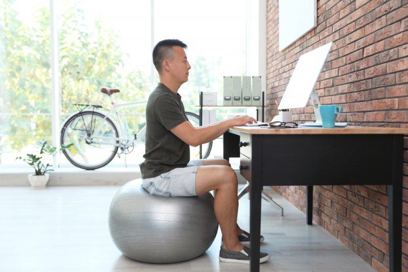 Un hombre utiliza una fitball para sentarse cuando trabaja en casa