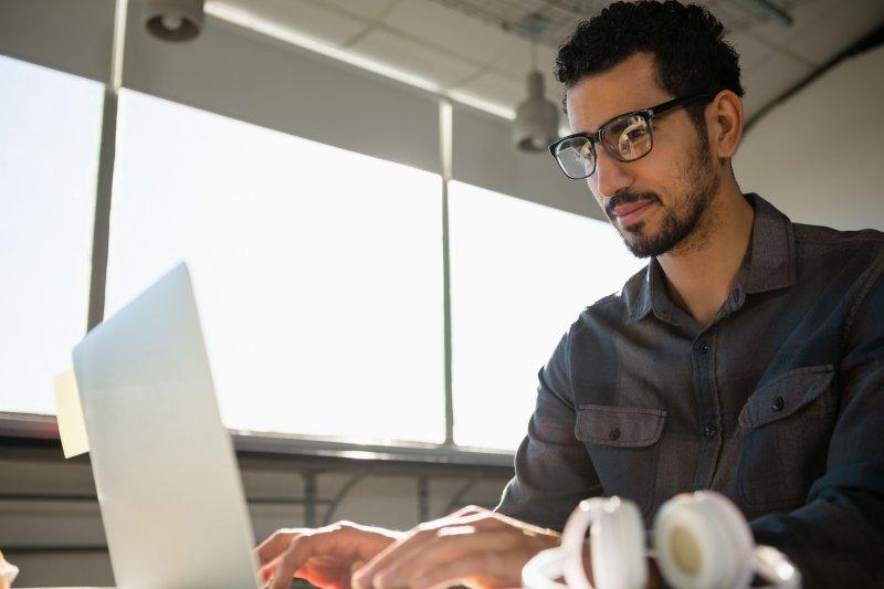 Un teletrabajador utiliza un ordenador portátil para escribir sus habilidades profesionales en su perfil de LinkedIn
