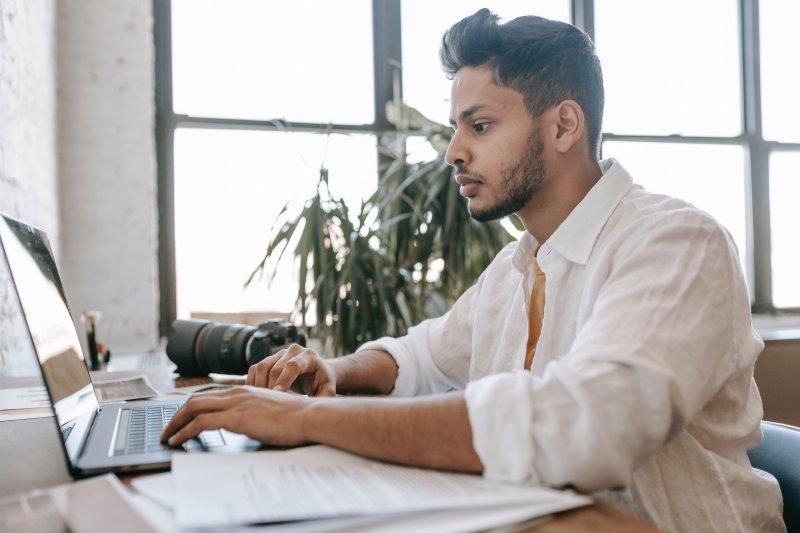 Un hombre joven escribe en su ordenador portátil un mensaje a un reclutador en LinkedIn