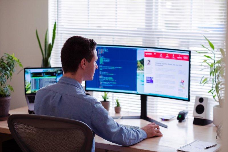 Un hombre teletrabaja con el ordenador en una habitación de su casa