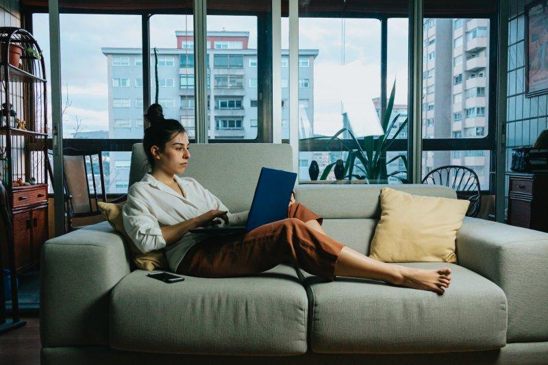 Una mujer realiza teletrabajo en el sofá de su casa con un ordenador portátil