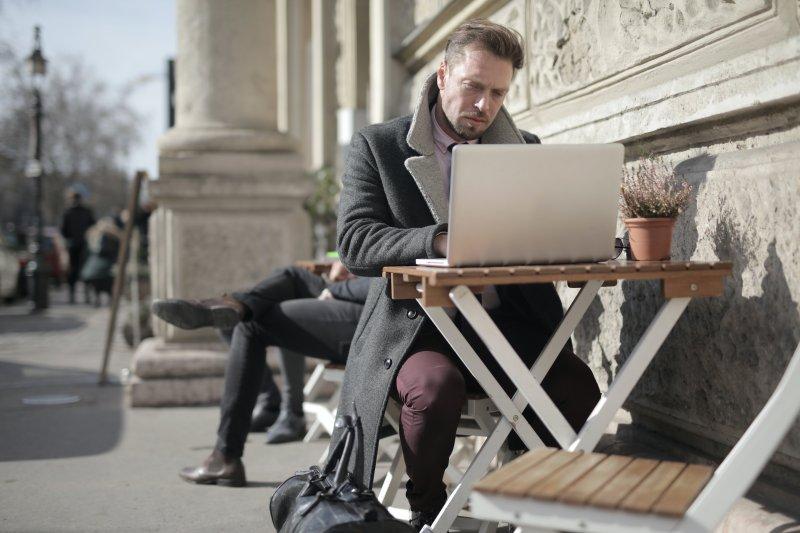 Un hombre trabaja con el ordenador portátil en la terraza de una cafetería