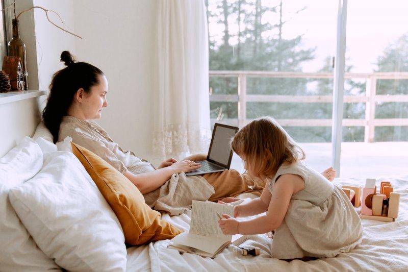 Mujer utiliza un ordenador portátil para trabajar en el dormitorio mientras su hija juega en la cama
